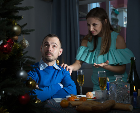 Portrait of adult couple quarreling at home near table with Christmas dinner