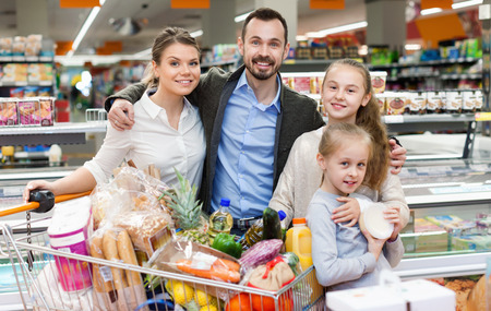 Happy  positive smiling family is standing with cart with products in the supermarket. Stok Fotoğraf