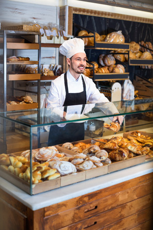 Cheerful man baker showing warm tasty croissant in bakery