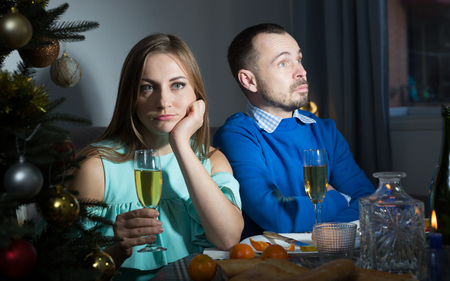 Portrait of man and woman having boring dinner at Christmas night