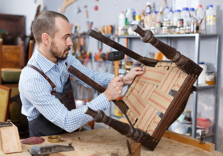 Concentrated craftsman using carpentry tools for restoration old armchair in workshop Archivio Fotografico