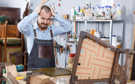 Annoyed workman dissatisfied with quality of leather for upholstering chair in repair furniture workshop