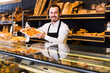 Smiling confectioner offers a taste of cakes in a bakery