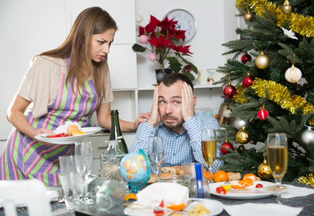 Young displeased woman clearing table after Christmas celebration and scolding drunk man sitting at table