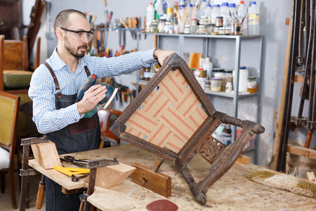 Professional carpenter engaged in restoring antique furniture using instruments Stock Photo