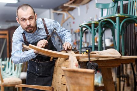 Skilled workman working at repair shop, restoring antique armchair