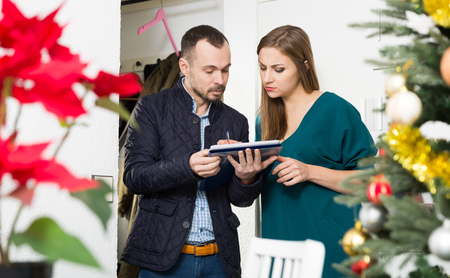 Young woman participating in survey conducted by male social worker at home before New Year Stock Photo