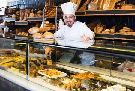Cheerful male baker showing assortment of bakery Imagens