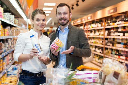 Happy couple is standing with products in milk department in the supermarket