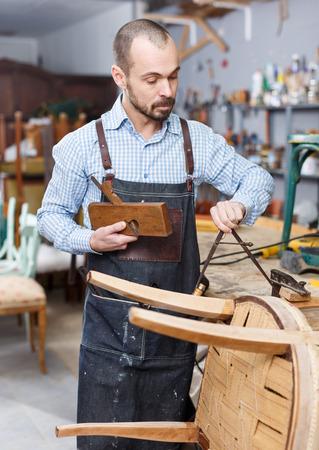 Craftsman measuring vintage armchair for restoration in workshop