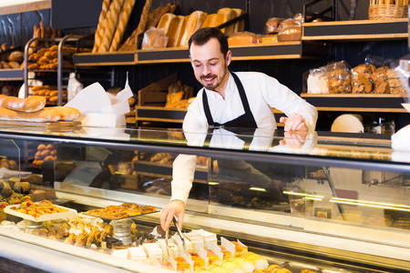 happy italian  male shop assistant demonstrating fresh delicious pastry in bakery Banco de Imagens