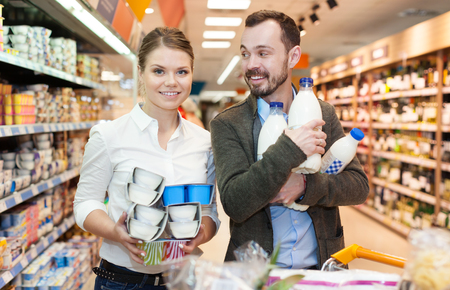 Happy couple is standing the with milk in supermarket Stok Fotoğraf