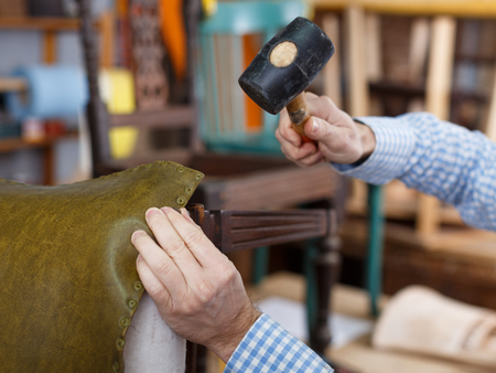 Close up of carpenter hands working with hammer in furniture workshop