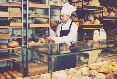 Young man is offering fresh tasty croissant in bakery.