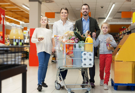 Smiling couple with kids is standing with purchases in the supermarket