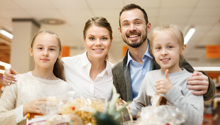Man with wife and their children are holding a purchases in a supermarket