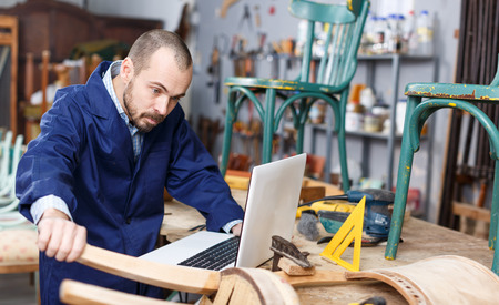 Professional young man carpenter using laptop while repairing antique furniture in workshop