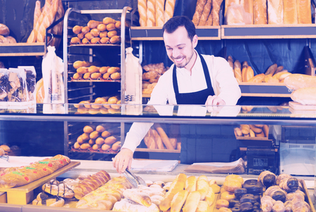 Smiling young male seller offering fresh tasty bun in bakery