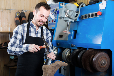 Smiling male professional worker using instruments for fixing in footwear repair workshop Imagens
