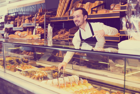 Positive adult male seller offering fresh tasty bun in bakery