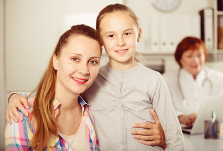 Adult female doctor leading medical appointment the young woman and child Stock Photo