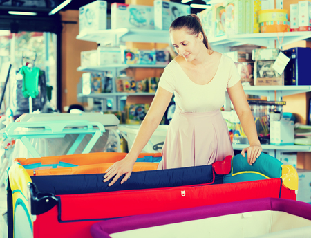 Young pregnant female looking for playpen at infant shop