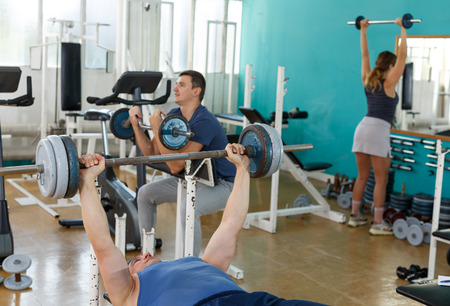 Sporty man practicing bench press with barbell in gym