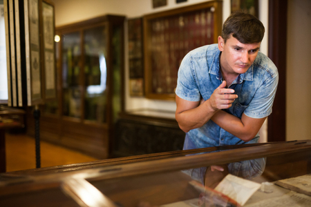 Man looking at stands with exhibits in historical museum hall