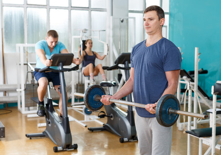 Muscular young man practicing with barbell in sport club
