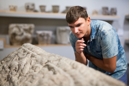 Man looking at stone architectural elements of Ancient Greece in historical museum hall