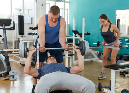 Muscular man in sportswear doing bench press with help of coach in gym Stock Photo