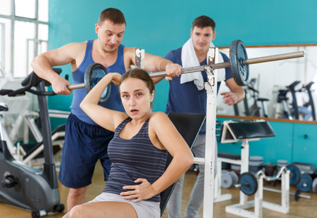 Sporty men helping injured during practicing with barbell young woman in gym