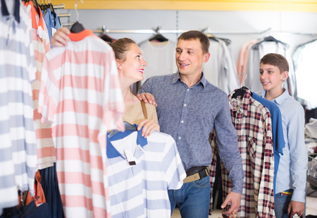 positive man, woman and boy stands near clothes and choosing man shirt in the boutique
