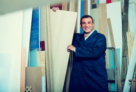 smiling man wearing protective workwear standing with plywood in store Фото со стока - 121421453