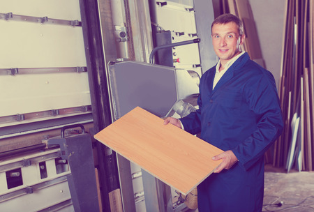 portrait of happy russian  man in uniform working on large automatic saw machinery indoors