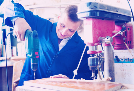 Positive glad diligent man wearing protective workwear operating automatic screwdriver in wood workshop