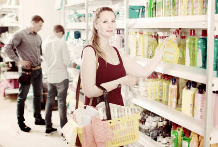 Happy young woman choosing detergent at a household goods supermarket Imagens
