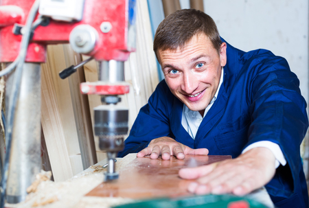 portrait of happy european man in uniform working with electrical screwdriver on plywood indoors Imagens