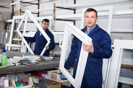 Young labour demonstrating finished PVC profiles and windows at factory