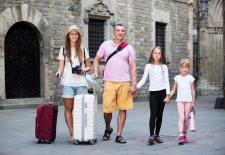 Family couple with two kids travelling together on European city, walking with baggage