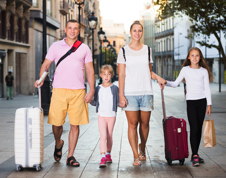 Parents with two kids travelling together on city, walking with luggage
