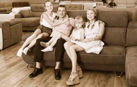 Big happy family is choosing new sofa in modern furniture store
