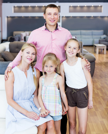 Glad family which is choosing new sofa in the store Stockfoto - 121452113