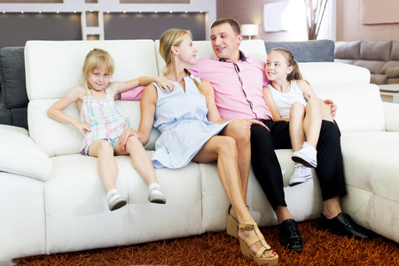 Happy young family which is choosing new sofa in the shop