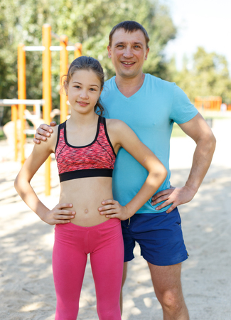 Smiling sporty man and tweenager girl posing together while exercising in summer park Stock Photo