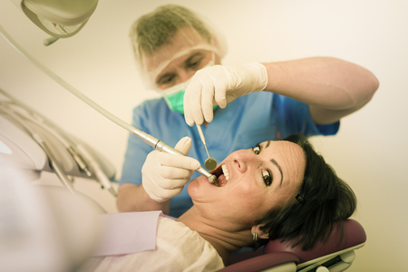 dentist professional filling teeth woman patient sitting in medical chair