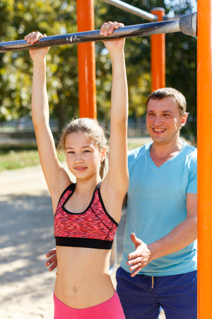 Sporty family of father and preteen girl training together outdoors, doing exercises on horizontal bar