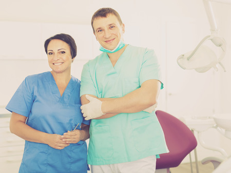 Dentist professional worker with assistant in medical room near chair