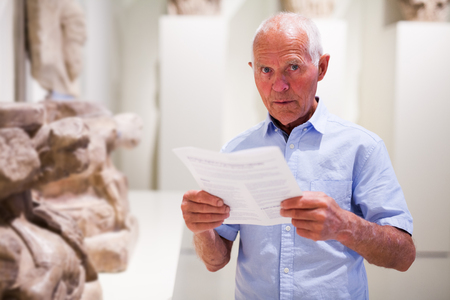 Thoughtful aged male with guide brochure exploring sculpture art pieces in gallery