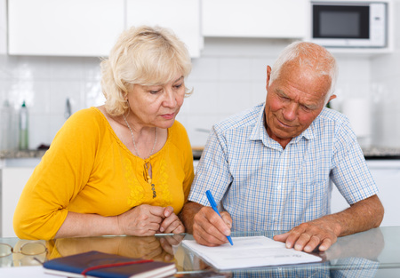 Portrait of mature couple in home interior filling up documents